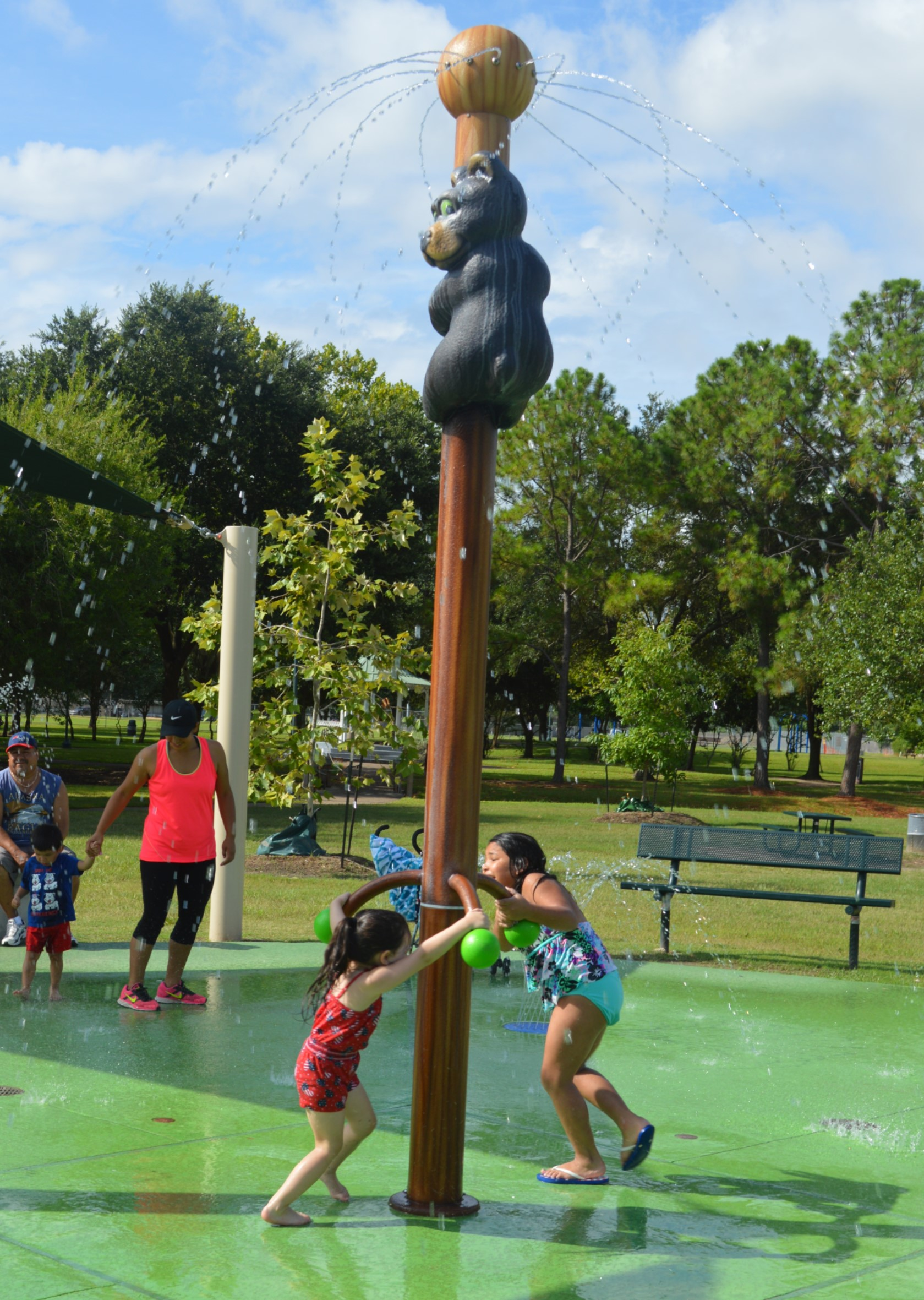 Kids playing outside at Splash Pad with adult in the background