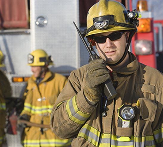 firefighter talking on radio with colleagues standing in the background